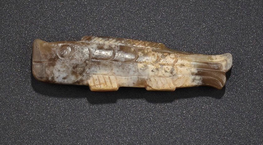 A MOTTLED CARAMEL JADE FISH-FORM PENDANT