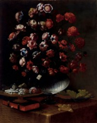 Chrysanthemums and other flowers in a glass vase with a dish of sweets, a book and a bowl on a table