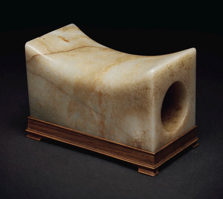 A mottled pale greenish-white and russet jade rectangular pillow, China, Ming dynasty (1368-1644) or later. 6⅞  in (17.4  cm) long. Sold for $60,000on 20 March 2019 at Christie's in New York