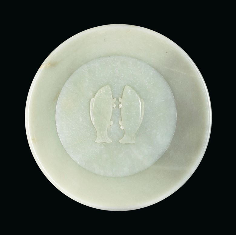 An important and extremely rare imperially inscribed greenish-white jade 'Twin Fish' washer, China, Qing Dynasty, 1786. Diameter 10  in (25.4  cm), hongmu stand. Sold for $2,895,000 on 20 March 2019 at Christie's in New York