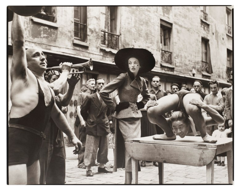 Richard Avedon (1923-2004), Elise Daniels with Street Performers, Suit By Balenciaga, Le Marais, Paris, 1948. Gelatin silver print, printed 1978. Sheet 14¼ x 17⅞ in (36.2 x 45.3 cm). Estimate $15,000-25,000. Offered in  Fashion Photo, 2-11 December 2019, Online