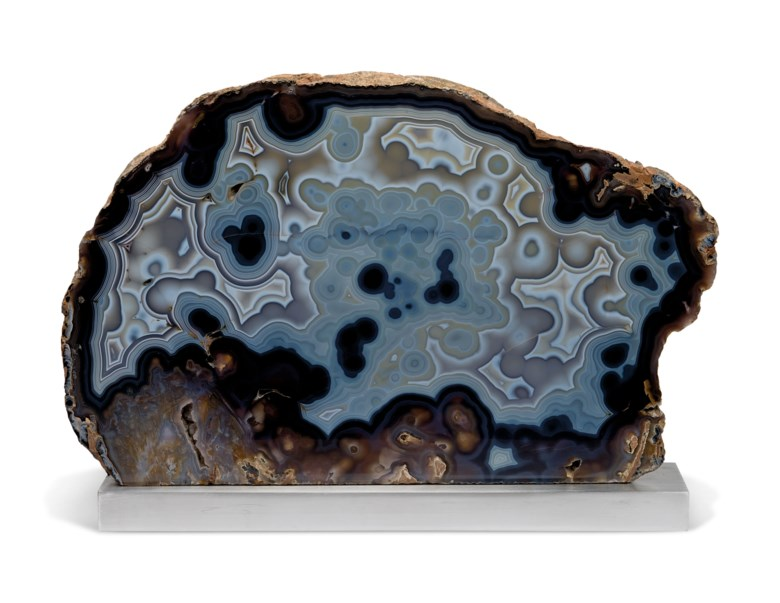 A large polished agate slice, Minas Gerais, Brazil. 18 x 27½ x 3 in (46 x 70 x 7.5 cm), 20 x 27.5 x 4 in (51 x 70 x 10 cm) on base. Estimate £3,000-5,000. Offered in  Sculpted by Nature Fossils, Minerals and Meteorites, 14-28 October 2020, Online