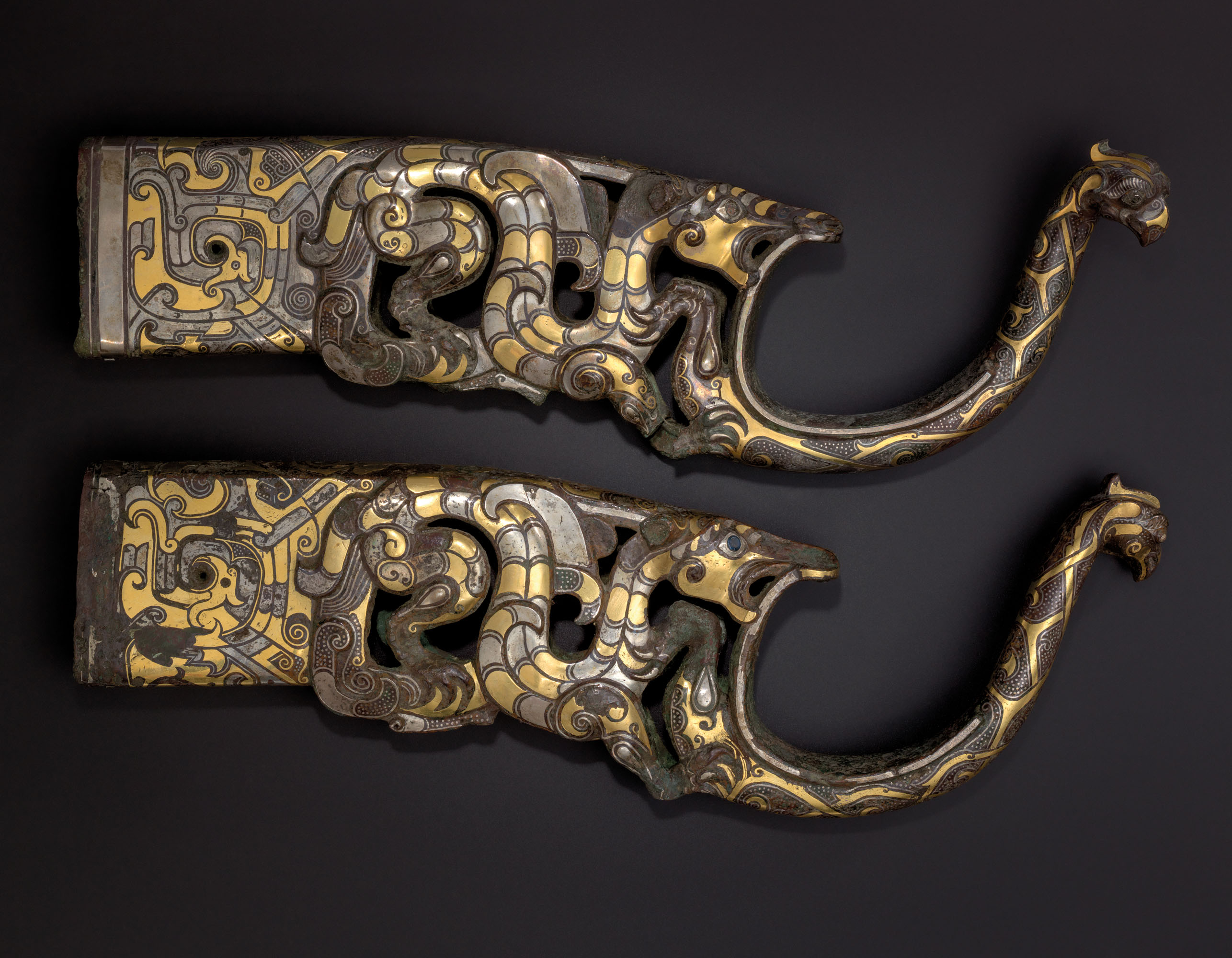 A RARE AND MAGNIFICENT PAIR OF GOLD AND SILVER-INLAID BRONZE CHARIOT FITTINGS