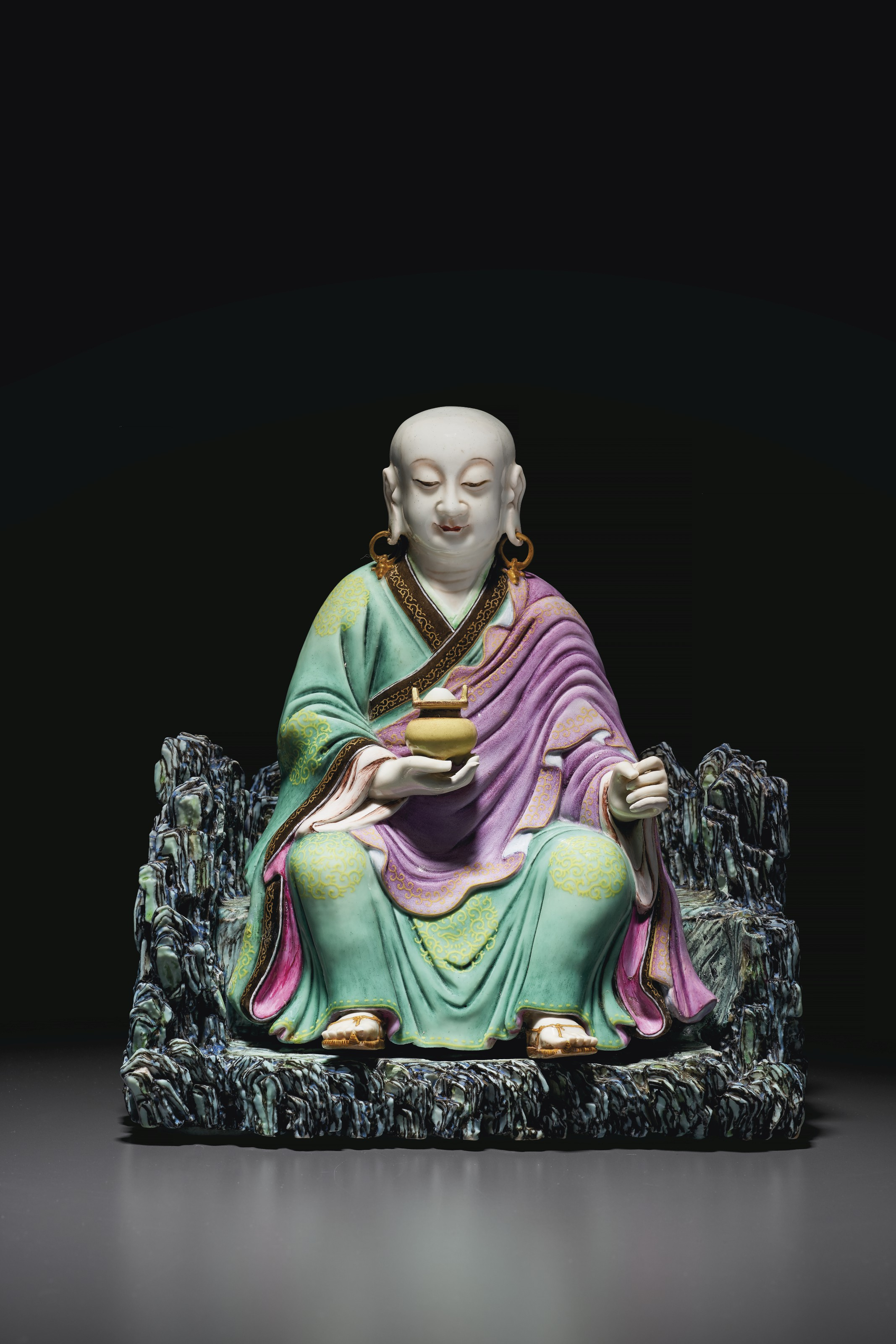 AN EXCEEDINGLY RARE AND SUPERBLY MODELED FAMILLE ROSE FIGURE OF A SEATED LUOHAN