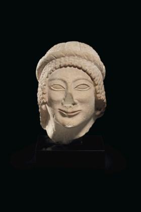 A CYPRIOT LIMESTONE FEMALE HEAD