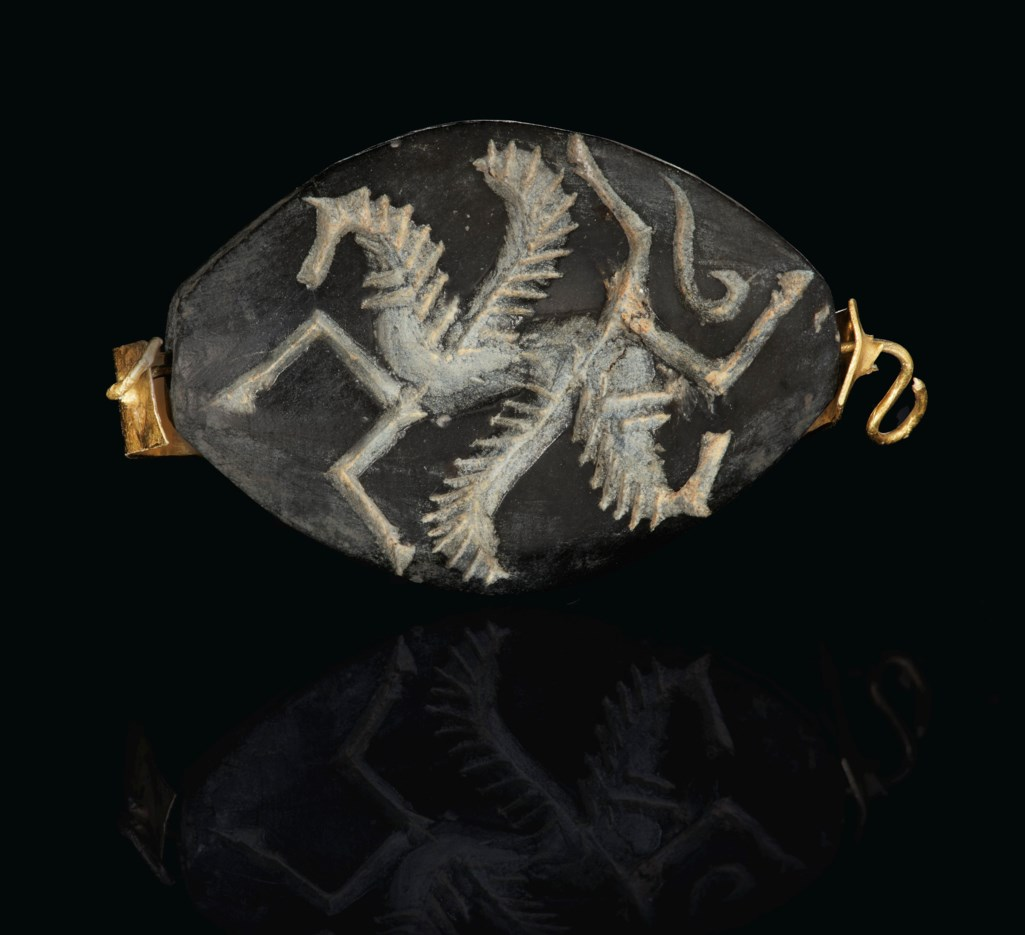 """A GREEK GOLD AND BLACK STEATITE AMYGDALOID """"ISLAND GEM"""" FINGER RING WITH WINGED HORSE FOREPARTS"""