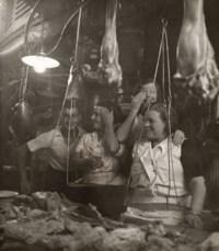 Vendeuses et vendeur riant derrière leur étal de charcuterie, Barcelone, 1933
