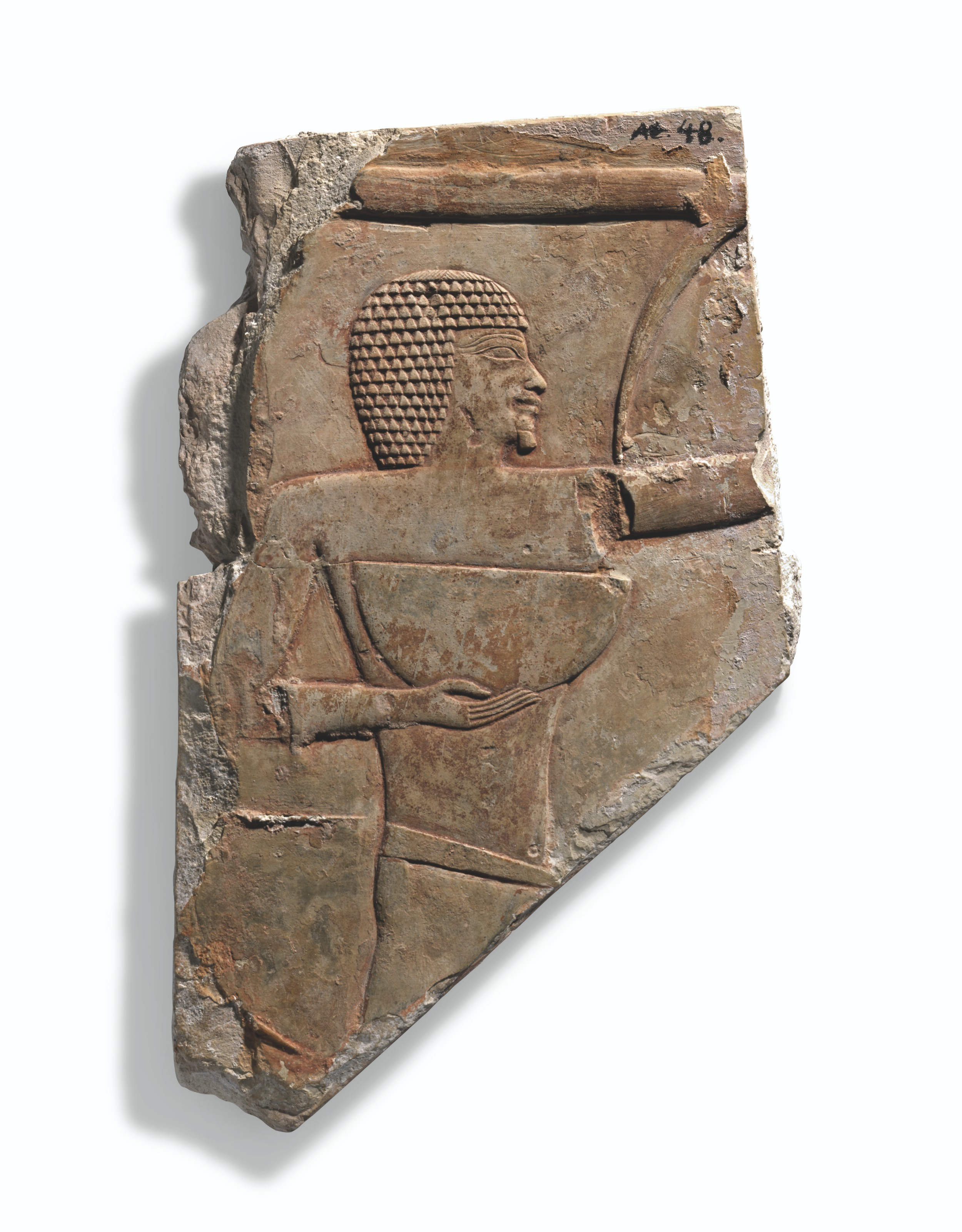 AN EGYPTIAN LIMESTONE RELIEF FRAGMENT WITH MAN HOLDING A BOWL