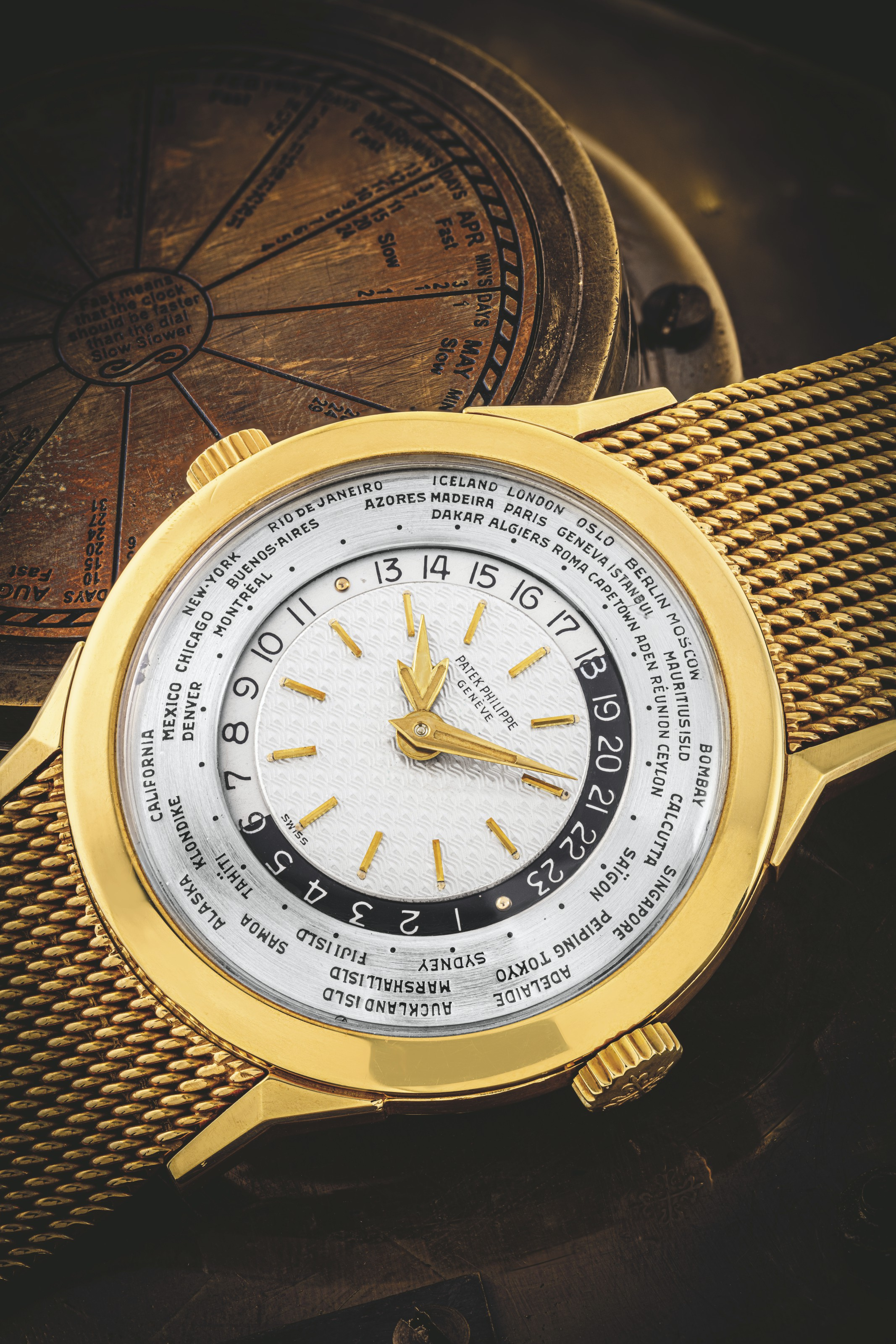 PATEK PHILIPPE. AN EXCEPTIONALLY RARE AND IMPORTANT 18K GOLD TWO CROWN WORLD TIME WRISTWATCH WITH 24 HOUR INDICATION AND BRACELET