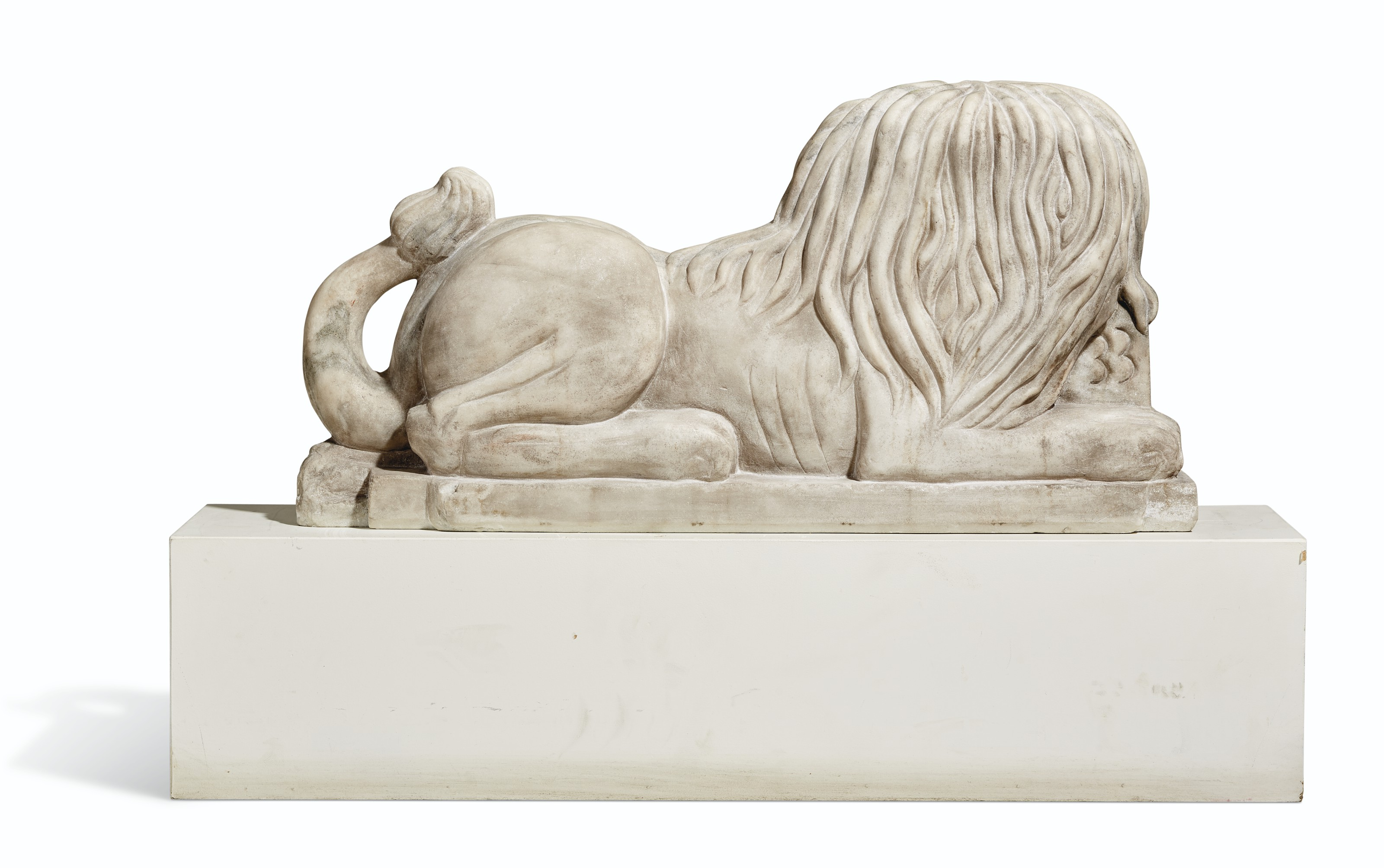 A CARVED WHITE MARBLE RECLINING LION