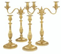 A PAIR OF GEORGE III SILVER-GILT TWO-LIGHT CANDELABRA AND A PAIR OF MATCHING CANDLESTICKS
