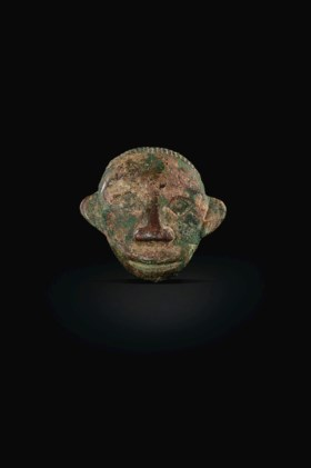 AN UNUSUAL SMALL BRONZE HUMAN MASK-FORM HARNESS ORNAMENT
