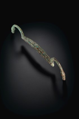 AN UNUSUAL TURQUOISE-INLAID BRONZE BOW-SHAPED FITTING WITH J