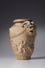 A TERRACOTTA VASE OF PUTTI WIT