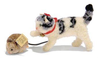 Steiff woolie pom pom calico cat chasing a Steiff woolie pom pom brown mouse
