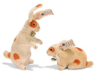 TWO STEIFF SMALL VELVET RABBITS, (3404 and 4410), white with brown spots, one lying and one begging, black boot button eyes, pink stitching, remains of ribbons with bells and FF buttons with white paper tags, circa 1909 --3¾in. (9.5cm.) high and 3in. (7.5cm.) long (some slight staining and white tags with a little wear)	 (2)