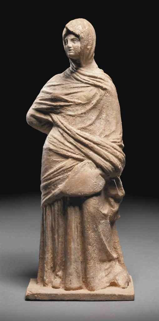 A GREEK TERRACOTTA FIGURE OF A WOMAN