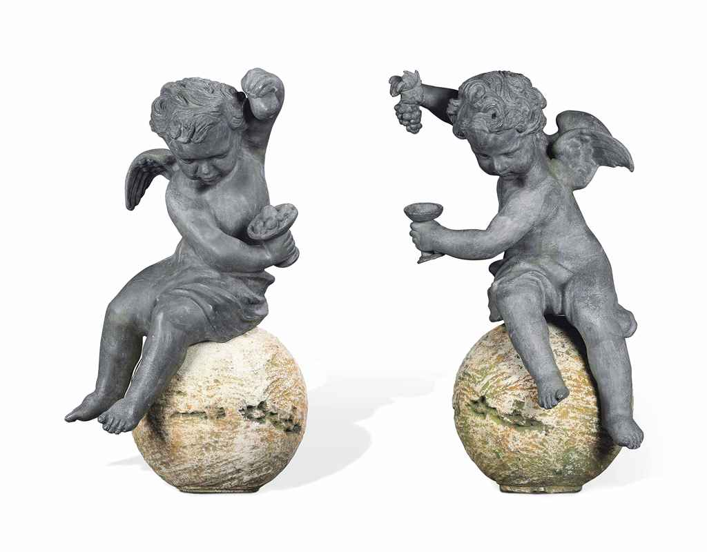 A PAIR OF LEAD PUTTI ON COMPOS
