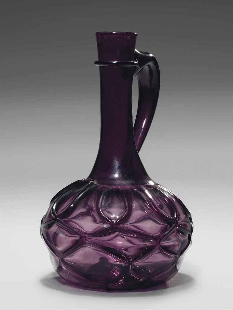 AN AMETHYST GLASS RIBBED CARAF