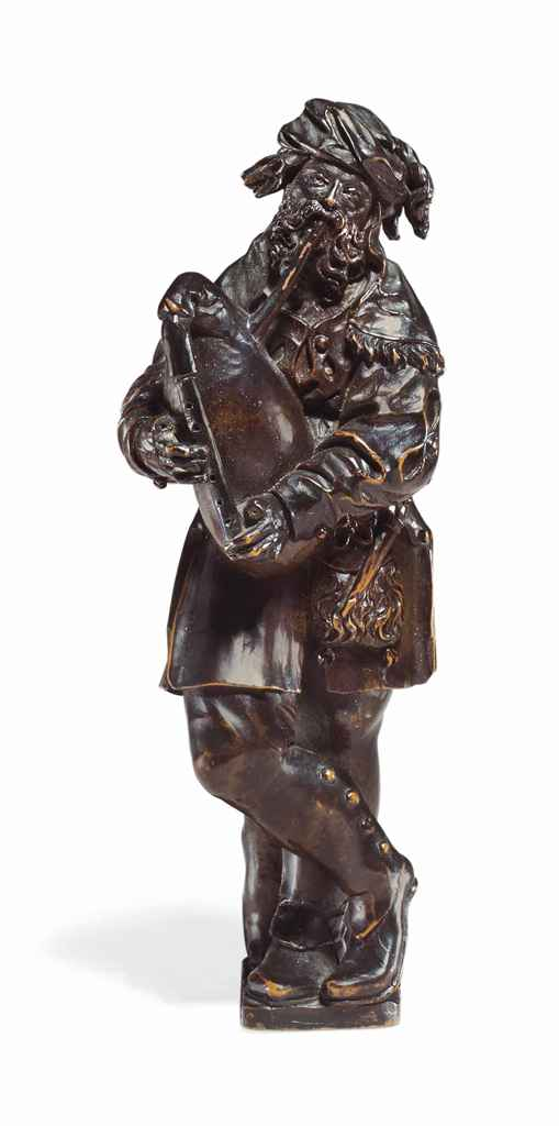 A CARVED BOXWOOD FIGURE OF A BAGPIPE PLAYER