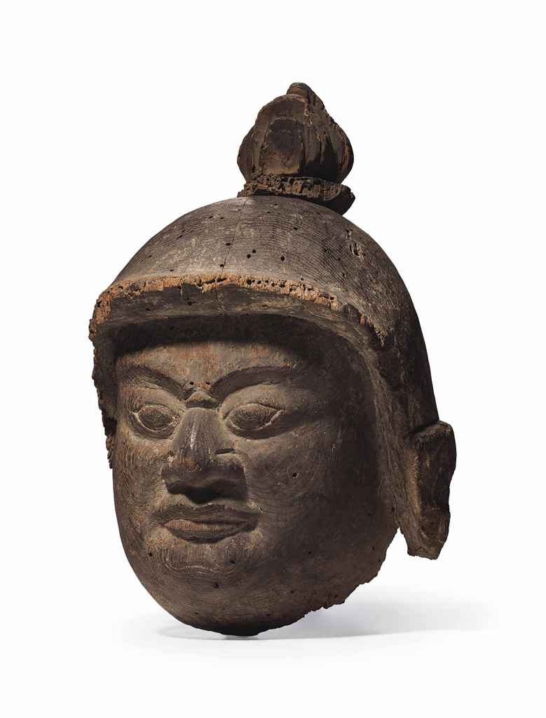 A carved-wood head of a Buddhist guardian