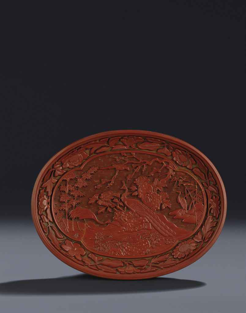 A RARE AND FINELY CARVED CINNABAR LACQUER 'EXOTIC BIRDS' OVA...