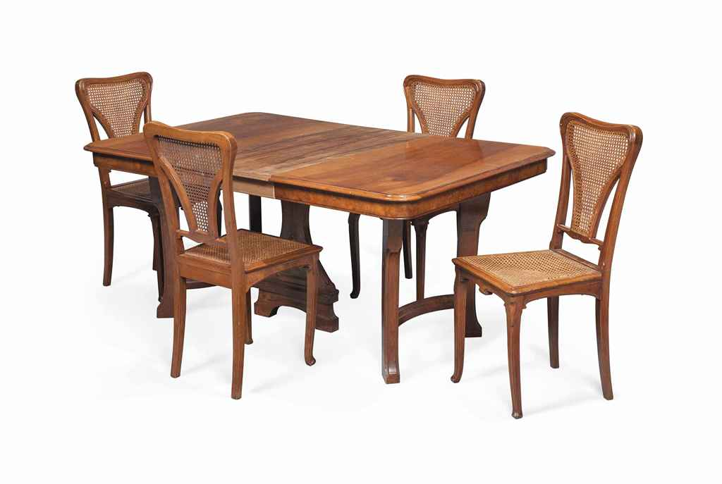 AN EDOUARD DIOT ART NOUVEAU WALNUT AND BRASS DINING TABLE AND