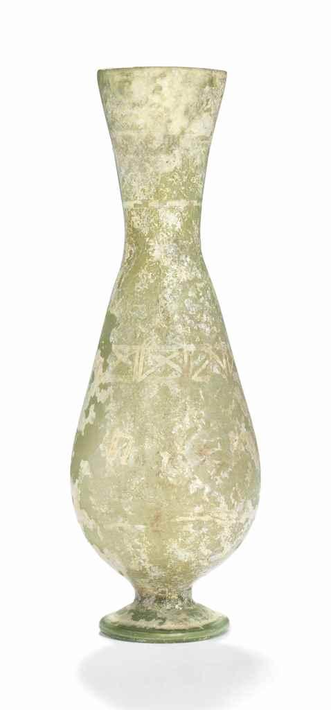 A LATE ROMAN GREEN GLASS WHEEL