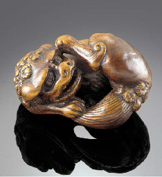 A wood netsuke of a shishi inc