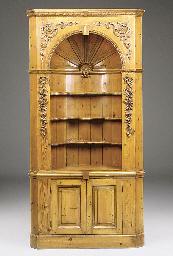 A carved pine corner cupboard,