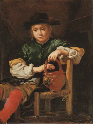A boy seated holding a red pot