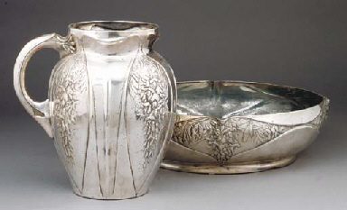 A SILVERED METAL PITCHER AND B