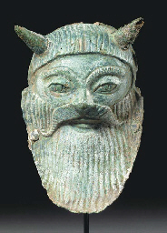AN ETRUSCAN BRONZE MASK OF ACH