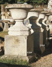 A SET OF FOUR BATH STONE URNS