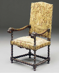 AN OAK CARVED OPEN ARMCHAIR