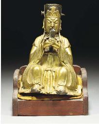 A gilt-bronze figure of a high