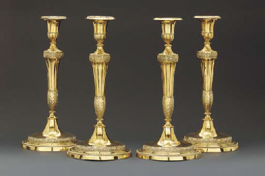 A set of four George III silver-gilt candlesticks