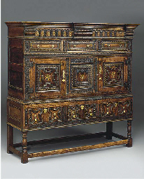 An oak and inlaid cupboard on