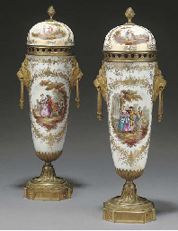 A PAIR OF GILTMETAL MOUNTED PORCELAIN ORNAMENTAL URNS AND CO...
