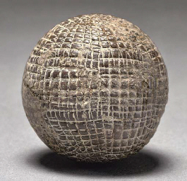 A HAND-HAMMERED GUTTY GOLF BALL