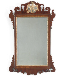 A GEORGE III MAHOGANY AND PARCEL GILT FRET CUT MIRROR