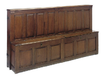 AN OAK PANELLED SETTLE