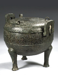 AN ARCHAIC BRONZE TRIPOD FOOD