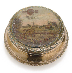 A CIRCULAR BRASS BOX WITH PAIN