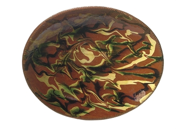 AN OVAL SLIP-DECORATED REDWARE