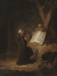 A hermit monk at prayer in a l