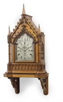 A GEORGE IV OAK GOTHIC REVIVAL STRIKING AND QUARTER-CHIMING BRACKET CLOCK, WITH WALL BRACKET