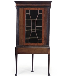 A MAHOGANY CORNER CUPBOARD ON