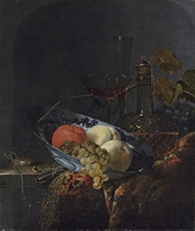 Grapes, peaches and an orange in a porcelain bowl, with a watch, nuts, a knife, a glass decanter, wine-glasses, grapes and a carpet on a wooden table