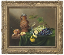 Grapes and a lemon on a pewter dish, with a wine glass, and a jug to the side, on a table